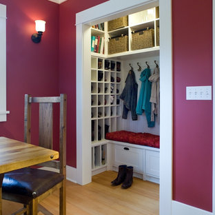 Inspiration for a mid-sized timeless gender-neutral light wood floor reach-in closet remodel in Seattle with recessed-panel cabinets and white cabinets