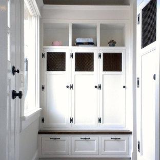 Ejemplo de armario vestidor unisex, clásico, pequeño, con armarios con paneles empotrados, puertas de armario blancas, suelo de ladrillo y suelo rojo