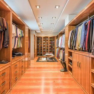 Idée de décoration pour un très grand dressing tradition pour un homme avec un placard sans porte, des portes de placard en bois brun, un sol orange et un sol en bois brun.