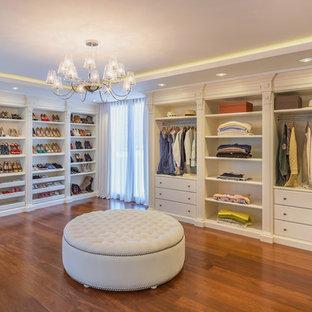 Diseño de armario vestidor de mujer, clásico, extra grande, con armarios abiertos, puertas de armario blancas, suelo marrón y suelo de madera en tonos medios