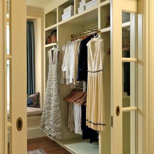 ボストンの男女兼用ヴィクトリアン調のおしゃれなフィッティングルーム (オープンシェルフ、無垢フローリング、ベージュのキャビネット、茶色い床) の写真