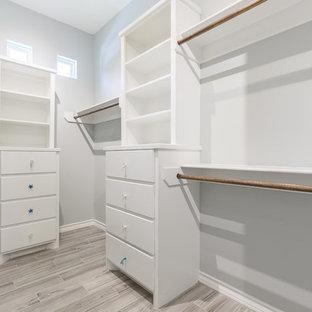 Immagine di una cabina armadio unisex costiera di medie dimensioni con ante lisce, pavimento in gres porcellanato e ante bianche