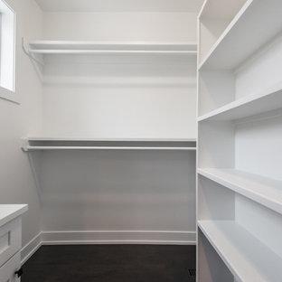 Inredning av ett modernt mellanstort walk-in-closet för könsneutrala, med skåp i shakerstil, vita skåp och svart golv