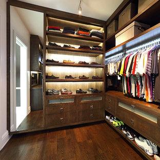 Immagine di una grande cabina armadio per uomo design con nessun'anta, ante in legno bruno e parquet scuro