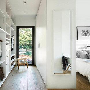 Modelo de armario vestidor unisex, contemporáneo, de tamaño medio, con armarios abiertos, puertas de armario blancas, suelo de madera en tonos medios y suelo marrón