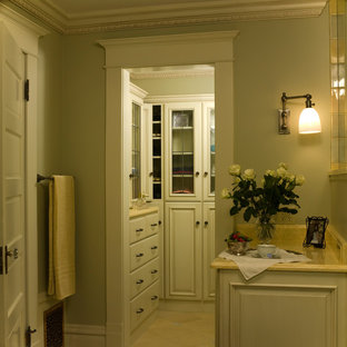 This is an example of a small traditional walk-in wardrobe for women in Denver with white cabinets and travertine flooring.