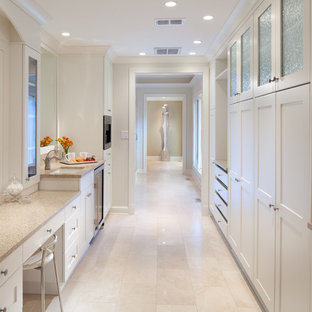 Design ideas for a classic dressing room in DC Metro with white cabinets and travertine flooring.