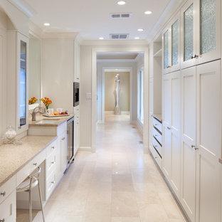 Стильный дизайн: парадная гардеробная в классическом стиле с белыми фасадами и полом из травертина - последний тренд