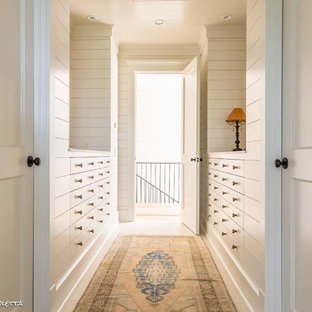 This is an example of a large wardrobe in Nashville with white cabinets and travertine flooring.