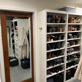 Imagen de armario vestidor unisex, minimalista, de tamaño medio, con armarios abiertos, puertas de armario blancas, suelo de baldosas de porcelana y suelo gris