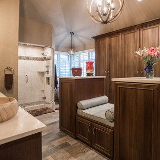 デンバーの大きいトランジショナルスタイルのおしゃれなウォークインクローゼット (落し込みパネル扉のキャビネット、中間色木目調キャビネット、ライムストーンの床、グレーの床) の写真