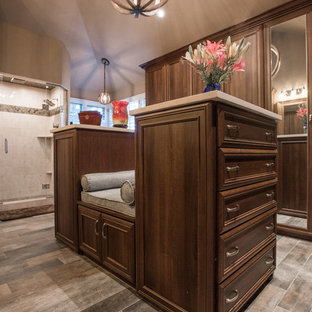 This is an example of a large transitional walk-in wardrobe in Denver with recessed-panel cabinets, medium wood cabinets, limestone floors and grey floor.