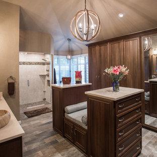 Diseño de armario vestidor tradicional renovado, grande, con armarios con paneles empotrados, puertas de armario de madera oscura, suelo de piedra caliza y suelo gris