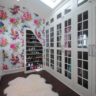 Ejemplo de armario vestidor de mujer, clásico renovado, con armarios tipo vitrina, puertas de armario blancas, suelo de madera oscura y suelo marrón
