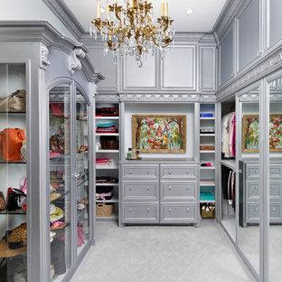 This is an example of an expansive victorian women's walk-in wardrobe in Houston with recessed-panel cabinets, grey cabinets and carpet.