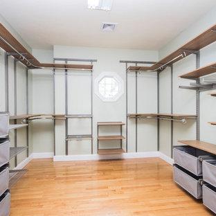 Foto de armario vestidor unisex, minimalista, extra grande, con armarios con paneles lisos, puertas de armario de madera oscura, suelo de madera en tonos medios y suelo marrón