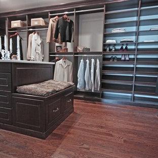 Foto di un'ampia cabina armadio unisex chic con ante con bugna sagomata, ante marroni, pavimento in legno massello medio e pavimento marrone
