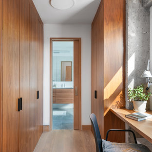 Trendy light wood floor and beige floor dressing room photo in New York with flat-panel cabinets and medium tone wood cabinets