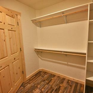 Foto de armario vestidor unisex, rural, de tamaño medio, con armarios abiertos, puertas de armario blancas, suelo de madera en tonos medios y suelo marrón