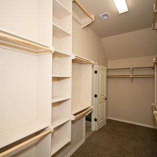 Aménagement d'un dressing classique de taille moyenne et neutre avec un placard sans porte, des portes de placard beiges et moquette.