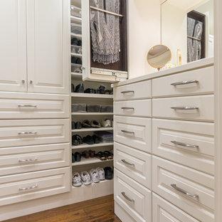 Großer, Neutraler Klassischer Begehbarer Kleiderschrank mit profilierten Schrankfronten, weißen Schränken und braunem Holzboden in Austin