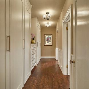 Diseño de armario vestidor unisex, clásico, de tamaño medio, con armarios estilo shaker, puertas de armario blancas, suelo de madera oscura y suelo marrón