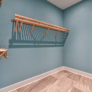 Immagine di una piccola cabina armadio unisex stile americano con pavimento in gres porcellanato e pavimento beige