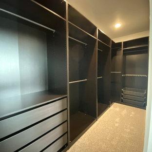 Foto de armario vestidor unisex, campestre, grande, con armarios con paneles lisos, puertas de armario de madera en tonos medios, moqueta y suelo beige