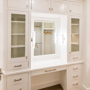 Design ideas for a small beach style gender-neutral walk-in wardrobe in New York with recessed-panel cabinets, white cabinets, light hardwood floors and beige floor.