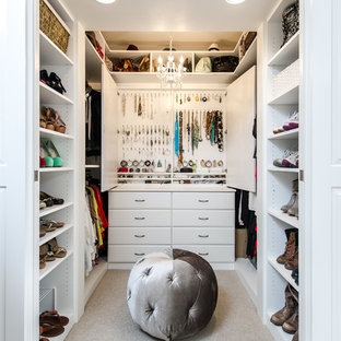 This is an example of a small traditional women's walk-in wardrobe in Los Angeles with raised-panel cabinets, white cabinets and carpet.