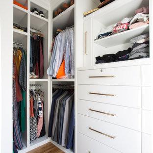 Modelo de armario vestidor unisex, minimalista, pequeño, con armarios con paneles lisos, puertas de armario blancas, suelo de madera clara y suelo multicolor