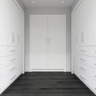 Imagen de armario vestidor moderno, grande, con armarios con paneles lisos, puertas de armario blancas, suelo de madera oscura y suelo negro