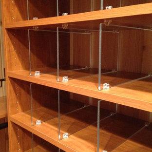 Ejemplo de armario vestidor unisex, clásico, grande, con armarios con paneles lisos, puertas de armario de madera oscura y suelo de madera en tonos medios