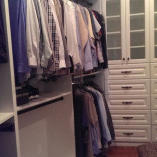 Modelo de armario vestidor unisex, tradicional, grande, con armarios con paneles con relieve, puertas de armario blancas y suelo de madera oscura