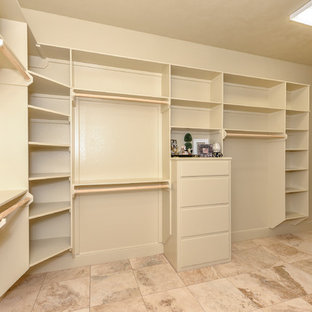This is an example of a large rustic gender neutral walk-in wardrobe in Austin with open cabinets, beige cabinets and travertine flooring.