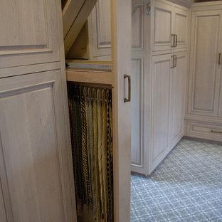 Diseño de armario vestidor unisex, tradicional, de tamaño medio, con armarios con paneles con relieve, puertas de armario de madera clara y moqueta