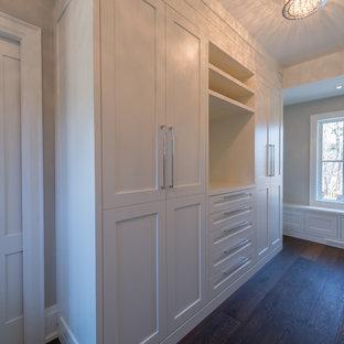 Idée de décoration pour un dressing room tradition de taille moyenne et neutre avec un placard à porte plane et des portes de placard blanches.