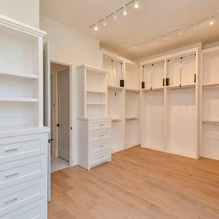 ヒューストンの広い男女兼用トラディショナルスタイルのおしゃれなウォークインクローゼット (オープンシェルフ、白いキャビネット、淡色無垢フローリング、ベージュの床) の写真