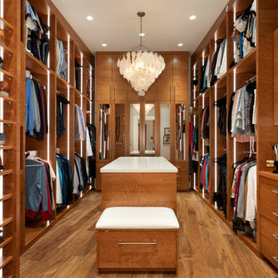 Photo of an expansive contemporary gender-neutral walk-in wardrobe in Vancouver with flat-panel cabinets, medium wood cabinets, brown floor and medium hardwood floors.
