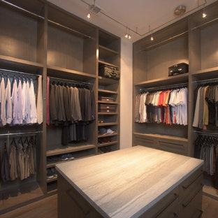 Cette image montre un grand dressing minimaliste pour un homme avec des portes de placard marrons, un placard à porte plane et un sol en bois peint.