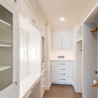 ニューヨークの小さい男女兼用ビーチスタイルのおしゃれなウォークインクローゼット (落し込みパネル扉のキャビネット、白いキャビネット、淡色無垢フローリング、ベージュの床) の写真
