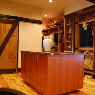 Diseño de vestidor unisex, de estilo americano, grande, con armarios abiertos, puertas de armario de madera en tonos medios y suelo de madera oscura