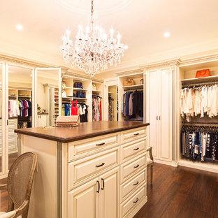 Modelo de vestidor unisex, clásico, grande, con armarios con paneles con relieve, puertas de armario beige, suelo de madera oscura y suelo marrón