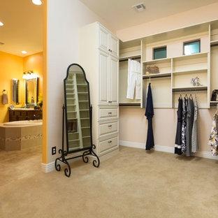 Inredning av ett klassiskt stort walk-in-closet för könsneutrala, med luckor med profilerade fronter, vita skåp, heltäckningsmatta och beiget golv