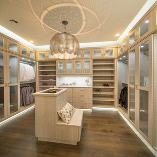 Example of a large trendy gender-neutral dark wood floor and brown floor walk-in closet design in San Diego with flat-panel cabinets and light wood cabinets