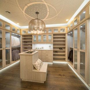 Immagine di una grande cabina armadio unisex contemporanea con ante lisce, ante in legno chiaro, parquet scuro e pavimento marrone