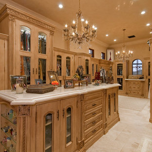 This is an example of an expansive traditional women's dressing room in Phoenix with glass-front cabinets, medium wood cabinets and travertine floors.