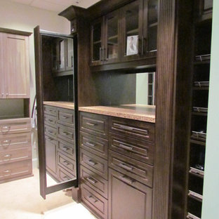 Inspiration for a large timeless gender-neutral carpeted and beige floor dressing room remodel in Atlanta with raised-panel cabinets and dark wood cabinets
