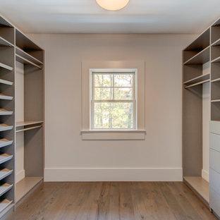Modelo de armario vestidor unisex, clásico renovado, grande, con armarios abiertos, puertas de armario grises y suelo de madera en tonos medios