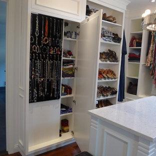 Foto di uno spazio per vestirsi unisex classico di medie dimensioni con ante bianche, pavimento in legno massello medio e ante con bugna sagomata